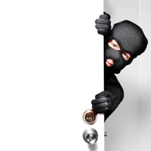 Home burglar opening house door